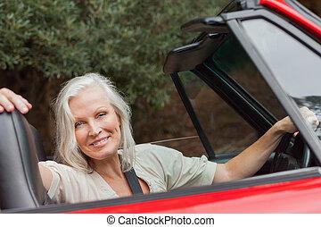 middelbare leeftijd , het poseren, het glimlachen, converteerbaar, vrouw, rood