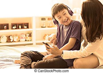 moeder, bed, zoon, muziek luisteren, slaapkamer