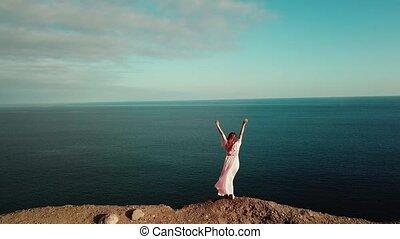 mooi, roze, turkoois, brunette, back., light., blauwe hemel, op, staand, het kijken, horizon, ondergaande zon , gran, handen, oceaan, jurkje, canaria., klip
