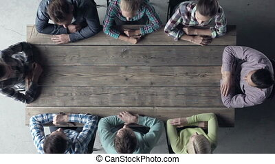 ongeveer, mensen zittende, op, duimen, tafel