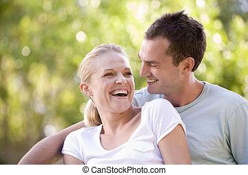 paar, zittende , lachen, buitenshuis