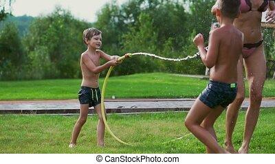 papa, vertragen, mamma, gezin, jongens, woning, motion., twee, water, hun, doordrenken, lachen, slang, achterplaats, het glimlachen, spelend, vrolijke