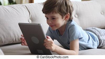 schattig, jongen, het liggen, sofa, alleen, tablet, gebruik, vrolijke , preschool