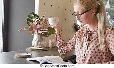 schattig, vertragen, thee, tafels, student, studerend , zittende , jonge, motie, venster, door, cafe., engelse , magazine, blonde, bril, drinkt, leafing