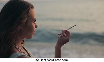 sigaret meisje, ondergaande zon , zee, smoking