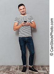 smartphone, beeld, lengte, volle, vasthouden, glimlachende mens