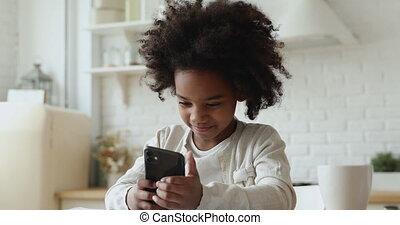 smartphone, geitje, vasthouden, het genieten van, afrikaan, beweeglijk, apps, gebruik, schattig, meisje
