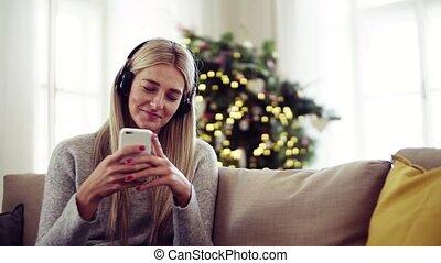 smartphone, headphones, jonge, time., vrouw, thuis, kerstmis
