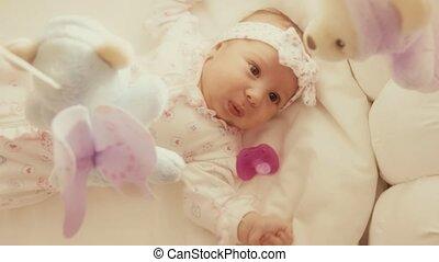speelbal, kinderbed, haar, beweeglijk, het kijken, defocused, baby meisje
