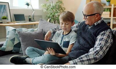 thuis, klesten, grootvader, cheerul, vrolijke , samen, gebruik, relaxen, geitje, tablet
