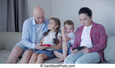 toepassingen, thuis, vreugde, smartphone, vrolijke , terwijl, hun, zittende , ouders, thuis, anderen, dwan, gebruik, kinderen, het genieten van, kleine, plezier, mijlen, hebben, elke, omhelzen, momenten, toneelstuk