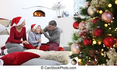 verfraaide, het glimlachen, kamer, gezin, zittende , openhaard, vrolijke , getrooste, verlicht, boompje, thuis, blij, zalige kerst, levend
