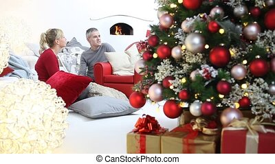 verfraaide, het glimlachen, kamer, gezin, zittende , vrolijke , levend, onder, verlicht, verpakte, thuis, pakketten, blij, boompje, vrolijk, cadeau, kerstmis