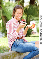 verzending, etende vrouw, appel, zittende , beweeglijk, tekst, park, jonge, telefoon boodschap
