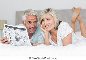 volwassen paar, krant, lezende , het glimlachen, bed