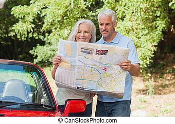 volwassen paar, lezende , het glimlachen, kaart