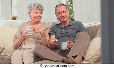 volwassen paar, mooi en gracieus, het schouwen tv