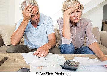 volwassen paar, thuis, gespannen, rekenmachine, rekeningen