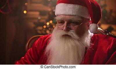 vrolijk, boompje, achtergrond., claus, terwijl, kerstman, het glimlachen, moderne, stoel, draagbare computer, zittende , zijn, kerstmis, werkende , claus., openhaard