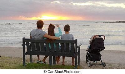 vrolijke , ondergaande zon , het zitten, ocean., bankje, gezin