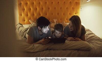 vrolijke , weinig; niet zo(veel), tablet, gezin, het schouwen rolprent, bed, zoon, computer, thuis, gebruik, slapende, spotprent, het liggen, voor