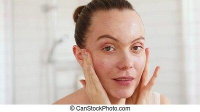 vrouw, aan het dienen, haar, moisturiser, gezicht, spiegel