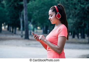 vrouw, park, het uitoefenen, terwijl, muziek luisteren, kaukasisch