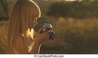 weinig; niet zo(veel), fototoestel, ondergaande zon , meisje
