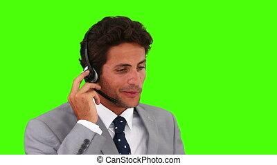 zakenmankostuum, grijs, op, het spreken, koptelefoon
