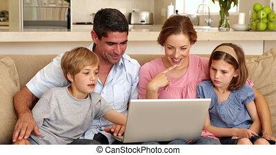 zittende , gezin, sofa, gebruikende laptop