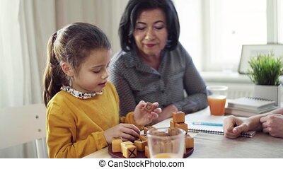zittende , grootmoeder, moeder, kleine, tafel, meisje, games., spelend, thuis