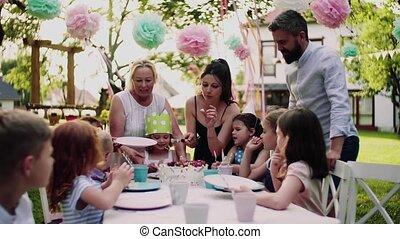zomer, feestje, kleine, buitenshuis, eten, cake., kinderen, tafel, zittende , tuin