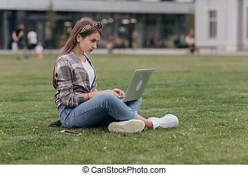 zomer, vrouw zitten, draagbare computer, park, jonge, terwijl, gekruiste, gedurende, verticaal, gebruik, benen, dag