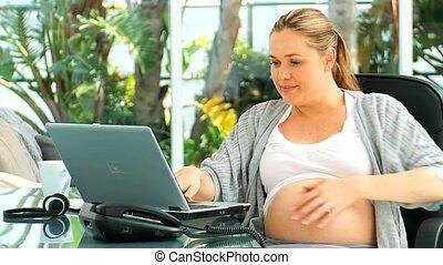 zwangere vrouw, draagbare computer, mooi en gracieus